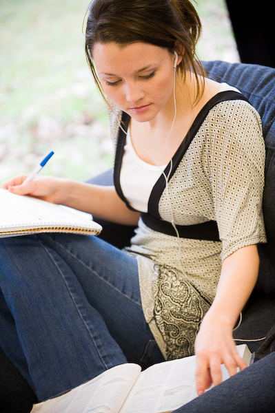 Photo of a female student studying wearing headphones